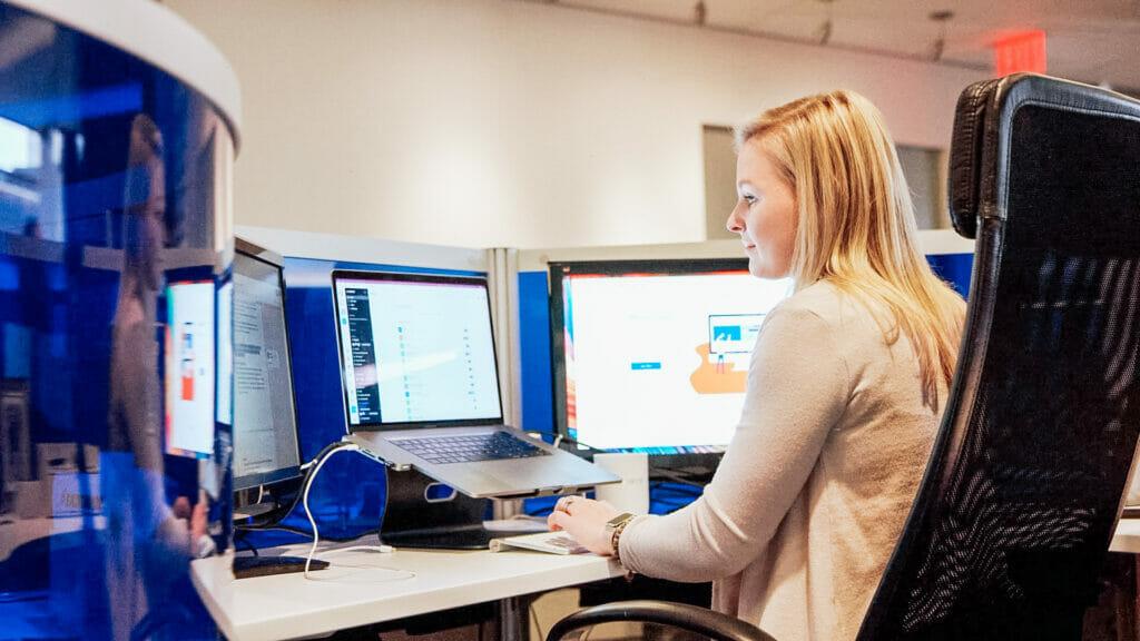 Chelsea working on laptop at blue desk